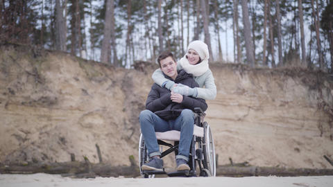 Positive handsome Caucasian boy in wheelchair and beautiful adult woman looking Live Action