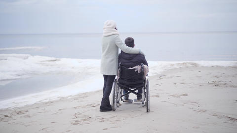 Back view of adult woman and handicapped man in wheelchair enjoying autumn day Live Action