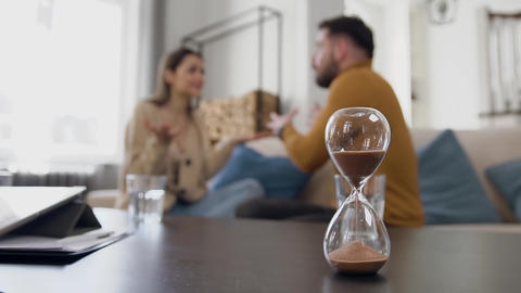 Sand clock calculating time where irritated young woman getting up from the Live Action