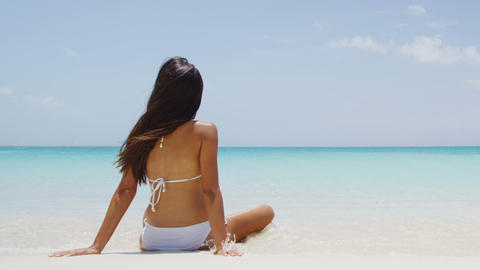 Travel vacation girl in white bikini relaxing on tropical beach sun tanning Live Action