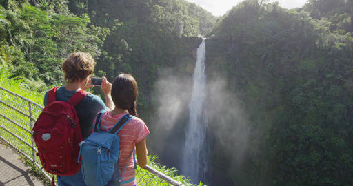 Tourist couple on Hawaii taking pictures of the famous Akaka Falls waterfall on Live Action