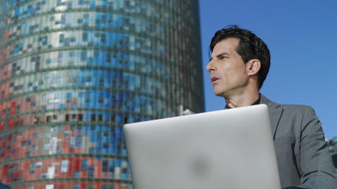 Businessman browsing internet on laptop outdoors. Professional using computer Live Action