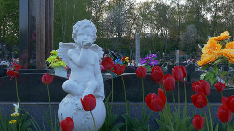 4K Ungraded: Plaster Statue of Angel Among Flowers in Front of Cemetery Footage
