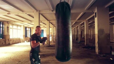 Strong athlete hits a punching bag. Medium shot Live Action
