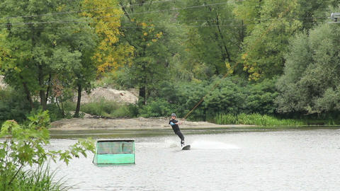 Wakeboarder jumps trampoline and lands on water surface towed Footage