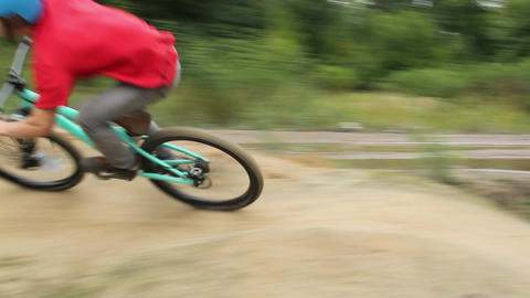 Bicycle BMX racer rides track in red shirt, spinning pedals Footage
