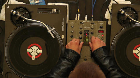 Nightclub DJ turns music really loud both hands, pan shot Footage