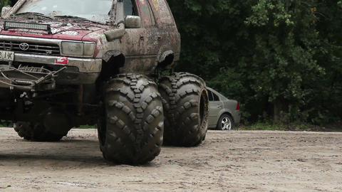 Moving large big-foot vehicle completely in mud and dirt wheels Live Action