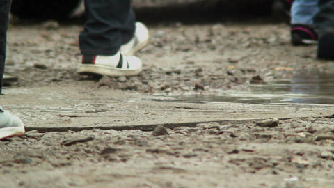 Slow-motion of feet, raindrops in dirty puddles, autumn concept Footage