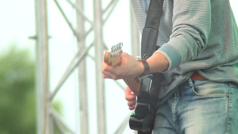 Musician with guitar playing on stage, day concert, rock Footage