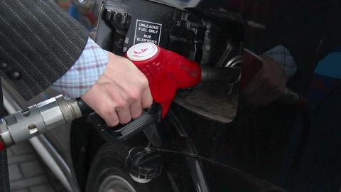 Businessman pulls out gasoline pistol fueling car petrol station Footage