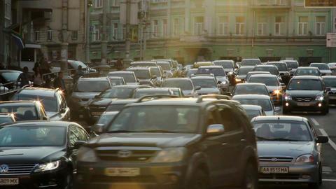 City cars vehicles lined traffic jam, dusk sun rays, movement Footage