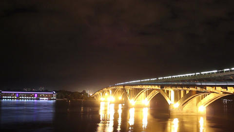 River bridge at night, cars drive water flows, clouds time-lapse Footage