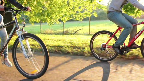 Riding bicycles young couple, dusk romantic relationships, sun Footage