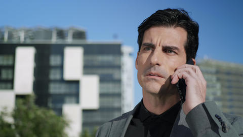 Businessman talking on cellphone outdoors. Executive using smartphone on street Live Action