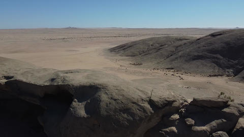 Aerial footage of the amazing desert in Namibia with grey sand and blue sky Live Action