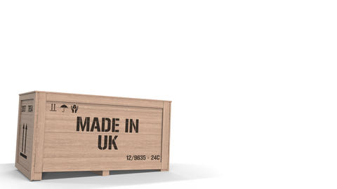 Wooden crate with printed MADE IN UK text isolated on light background. British Live Action