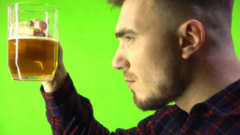Drunk man in a plaid shirt with a glass of beer on a green background Live Action