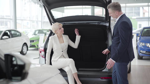 Elegant blond Caucasian woman sitting in car trunk and talking with trader in Live Action