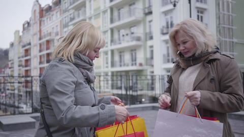 Portrait of positive middle-aged Caucasian women discussing purchases on city Live Action