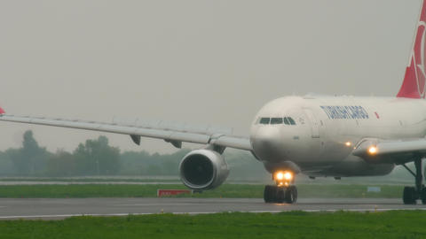 Airfreight slowing after landing at rainy weather Live Action