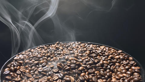 Smoke swirls over hot coffee beans. Slow motion Live Action