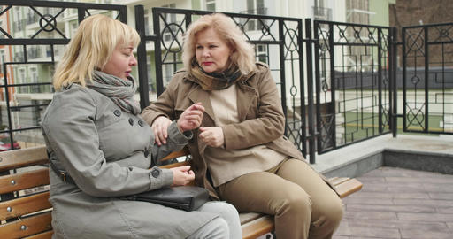 Worried senior Caucasian woman calming down female friend outdoors. Two retirees Live Action