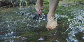 Slow motion of woman's feet wading river rapids, RED 4K Footage