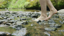 Slow motion of woman's feet stepping on river rocks, RED 4K Footage