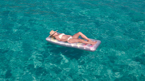 Young caucasian woman sun bathing on air mattress in crystal clear waters Footage