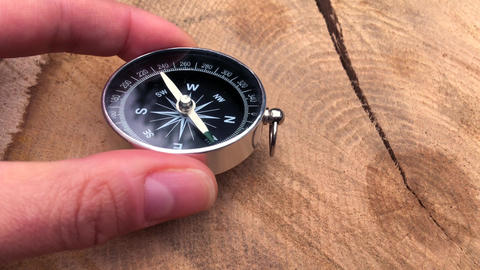Round metal compass in human fingers Live Action