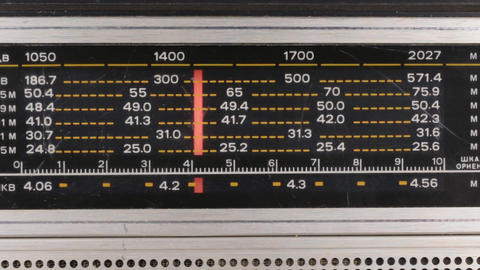 Tuning the frequency of the radio station on the old radio. The red arrow moves Live Action