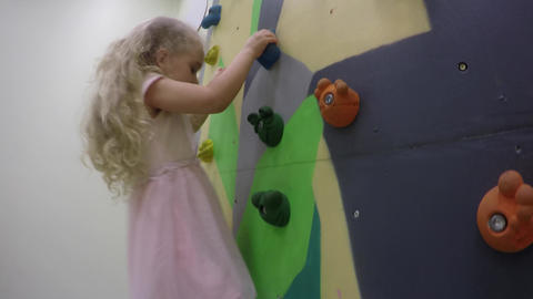 Young girl climbing up on an indoors climbing wall Live Action