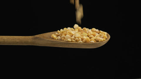Falling grain peas fills the spoon and fall out of a wooden spoon. Slow motion Live Action