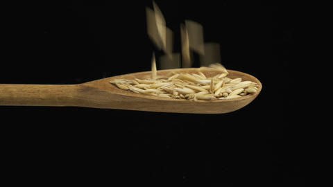 Falling grain oats fills the spoon and fall out of a wooden spoon. Slow motion Live Action