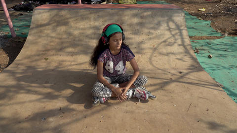 The girl goes in for sports and listens to music in India GIF