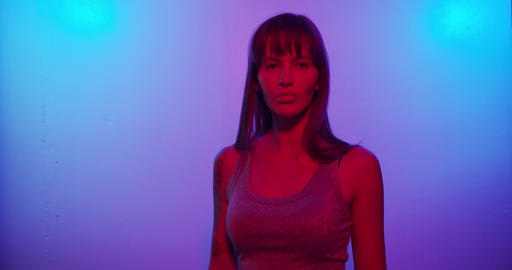 Fashion model girl Turns to the camera and looks in neon light Live Action