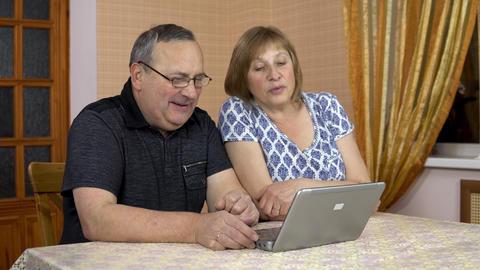 A man and a woman communicate with friends via video communication via a laptop Live Action