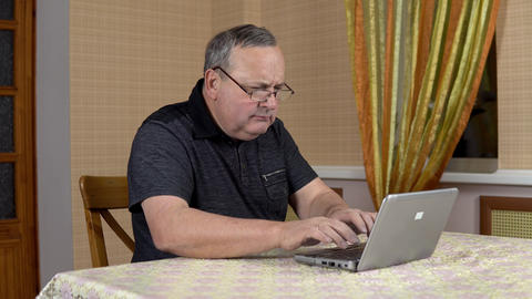 Man is using a laptop for the first time. The old man hardly uses a laptop Live Action