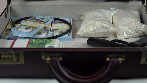 A man opens a case closeup. In an open case are dollars and drugs Live Action