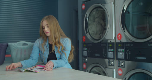 Young woman reading magazine while washing her laundry at laundromat Live Action
