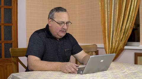 A man communicates with friends via video calling through a laptop. An old man Live Action