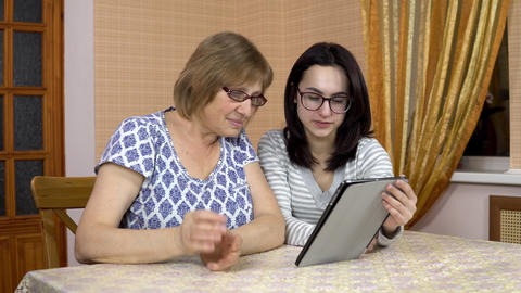 Daughter teaches mother how to use a tablet. A young woman shows her old mother Live Action