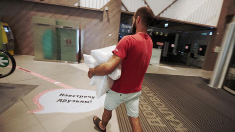 man carries bag with product of recycling materials in hall Live Action