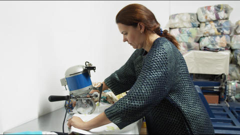 mature woman cuts cloth for recycling at workplace in room Live Action