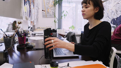 woman gives thermos to colleague in architectural office Live Action