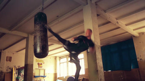 Male Athlete boxer punching bag with dramatic edgy lighting in a dark studio Footage