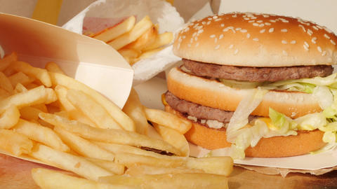 portion of unhealthy food, fast food, burger, fries rotating, turning Live Action