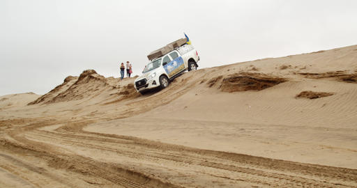Big white SUV is driving offroad in the desert, over the steep hill, 4k Live Action