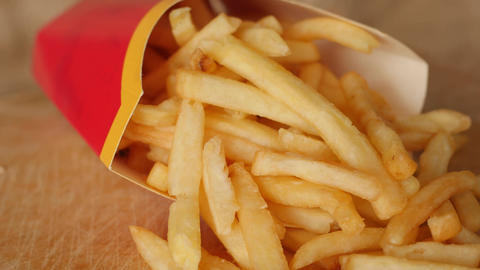 portion of unhealthy food, fast food, paper bag with fries rotating, turning Live Action